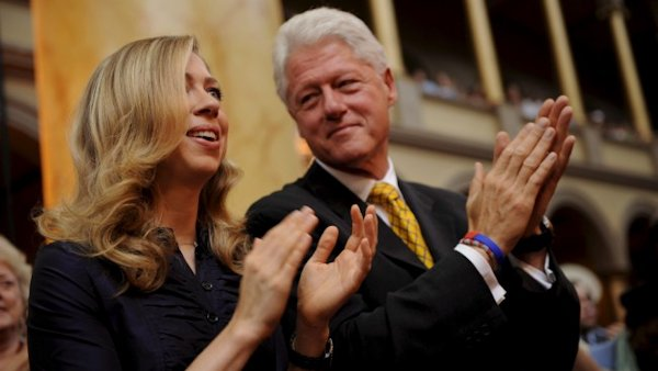Chelsea and Bill Clinton applauding